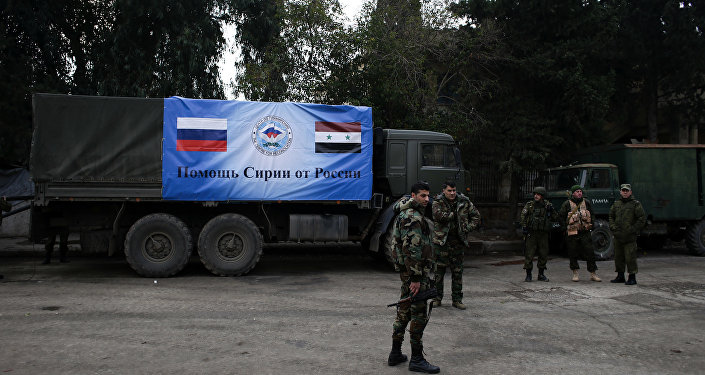 Russian and Syrian soldiers stand next to an aid convoy in Syria