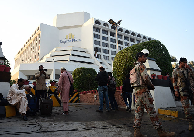 Guests are gather outside a Regent Plaza Hotel following a fire in the Pakistan's port city of Karachi on December 5, 2016