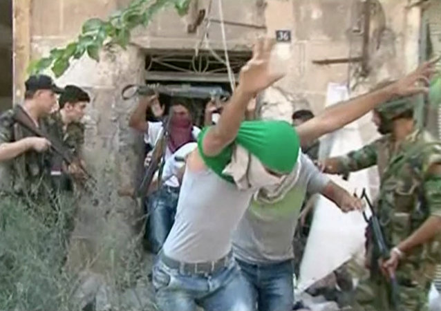 This still image from Syrian state TV video, shows young men with their faces covered surrendering to government forces, in Aleppo, Syria, Saturday, July 30, 2016