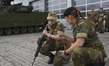 A female army recruit attends a base training at the armored battalion in Setermoen, northern Norway