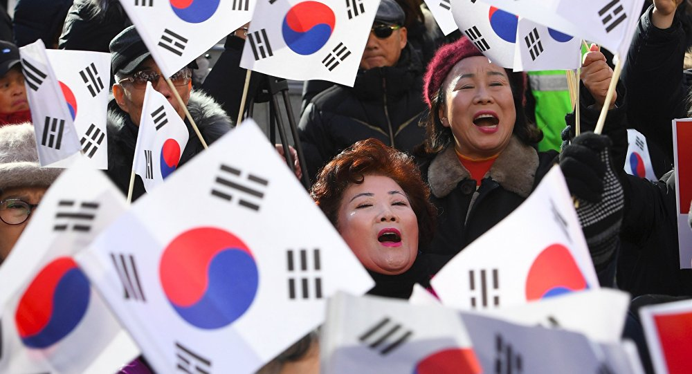 Supporters of South Korean President Park Geun-Hye wave the national flags during a rally against the impeachment of the president outside the ruling Saenuri Party in Seoul on December 6, 2016.