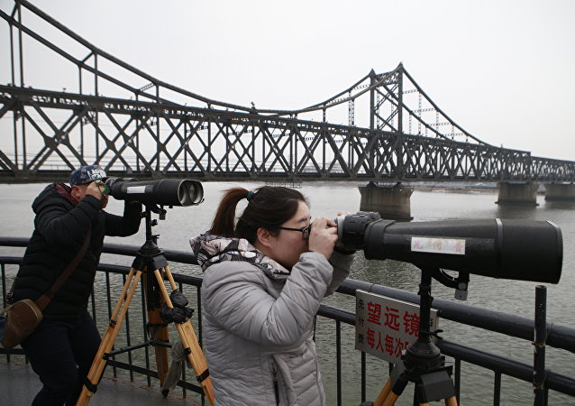 Chinese tourists watch the North Korean side across the Yalu River using telescopes in Dandong, Northeast China's Liaoning Province