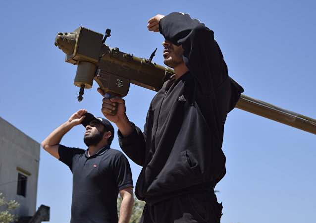 Rebel-fighters monitor the sky holding a man-portable air-defence system (MANPADS) in the Syrian village of Teir Maalah, on the northern outskirts of Homs, on April 20, 2016.