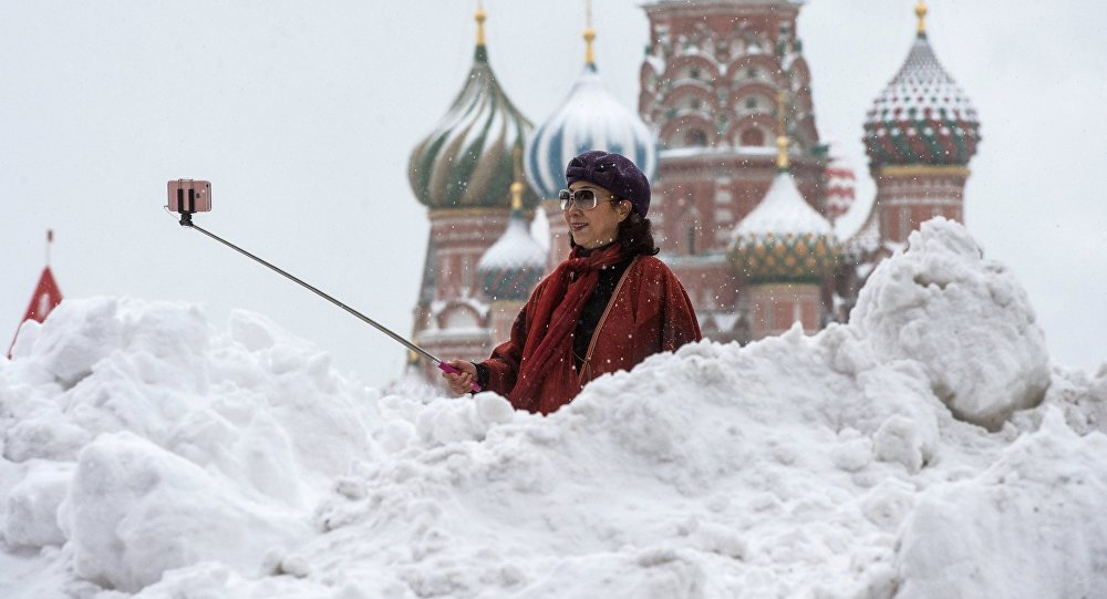 A woman is photographed near the St Basil Cathedral on the Red Square