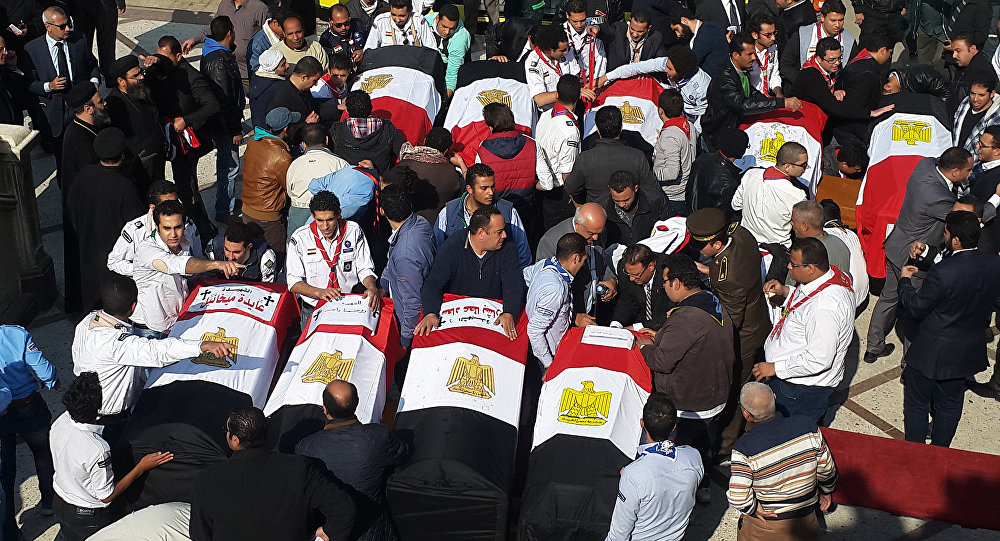 Egyptian mourners and officials stand next to the coffins of the victims of a bomb explosion that targeted a Coptic Orthodox Church the previous day in Cairo, at the end their funeral in the capital's Nasr City neighbourhood on December 12, 2016