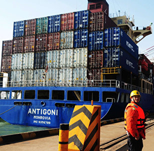 This picture taken on March 7, 2014 shows a man working beside a cargo ship in Qingdao port in Qingdao, east China's Shandong province
