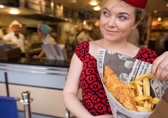 A person poses with fish and chips at Poppies fish and chip restaurant in east London on January 26, 2015.
