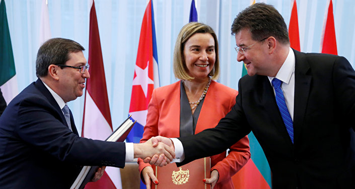 Cuba's Foreign Minister Bruno Rodriguez shakes hands with Slovakian Foreign Minister Miroslav Lajcak next to European Union foreign policy chief Federica Mogherini after signing a EU-Cuba Political Dialogue and Cooperation Agreement in Brussels, Belgium December 12, 2016