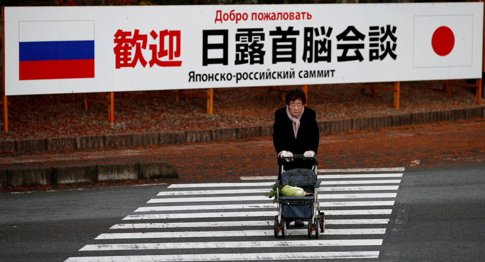 A woman walks in front of a sign board that reads Welcome Japan Russia summit meeting near a hot spring resort, the venue of the summit meeting between Japanese Prime Minister Shinzo Abe and Russian President Vladimir Putin, in Nagato, Yamaguchi prefecture, Japan, December 15, 2016.