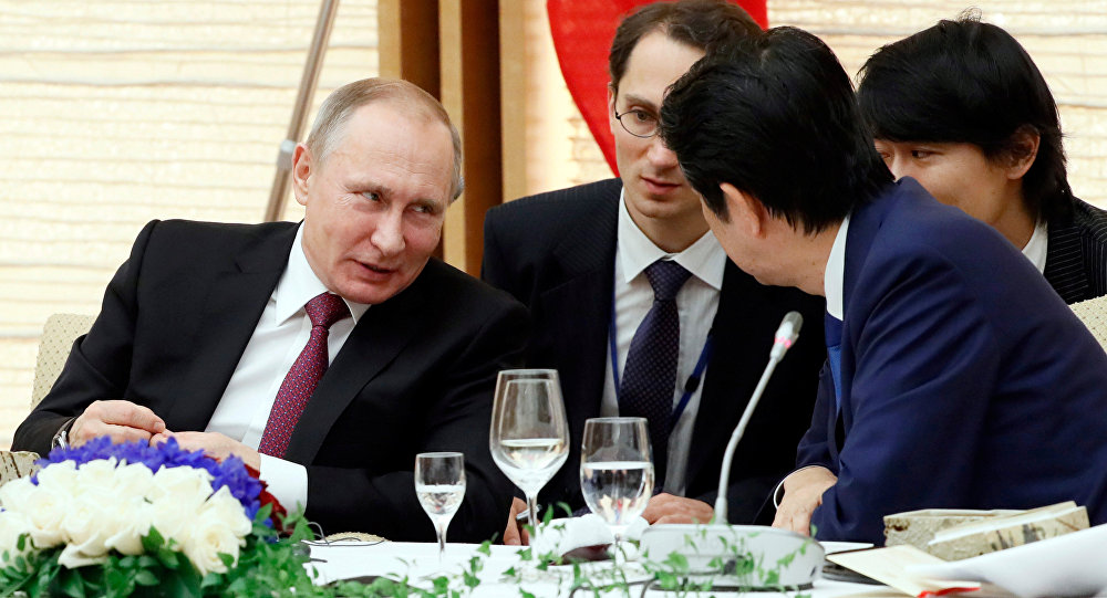 Russian President Vladimir Putin, left, confers with Japanese Prime Minister Shinzo Abe during a working lunch in Tokyo, Japan, Friday, Dec. 16, 2016.