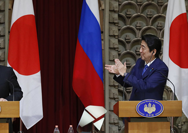 Japanese Prime Minister Shinzo Abe, right, applauds as Russian President Vladimir Putin reacts during their joint press conference in Tokyo, Japan, Friday, Dec. 16, 2016.