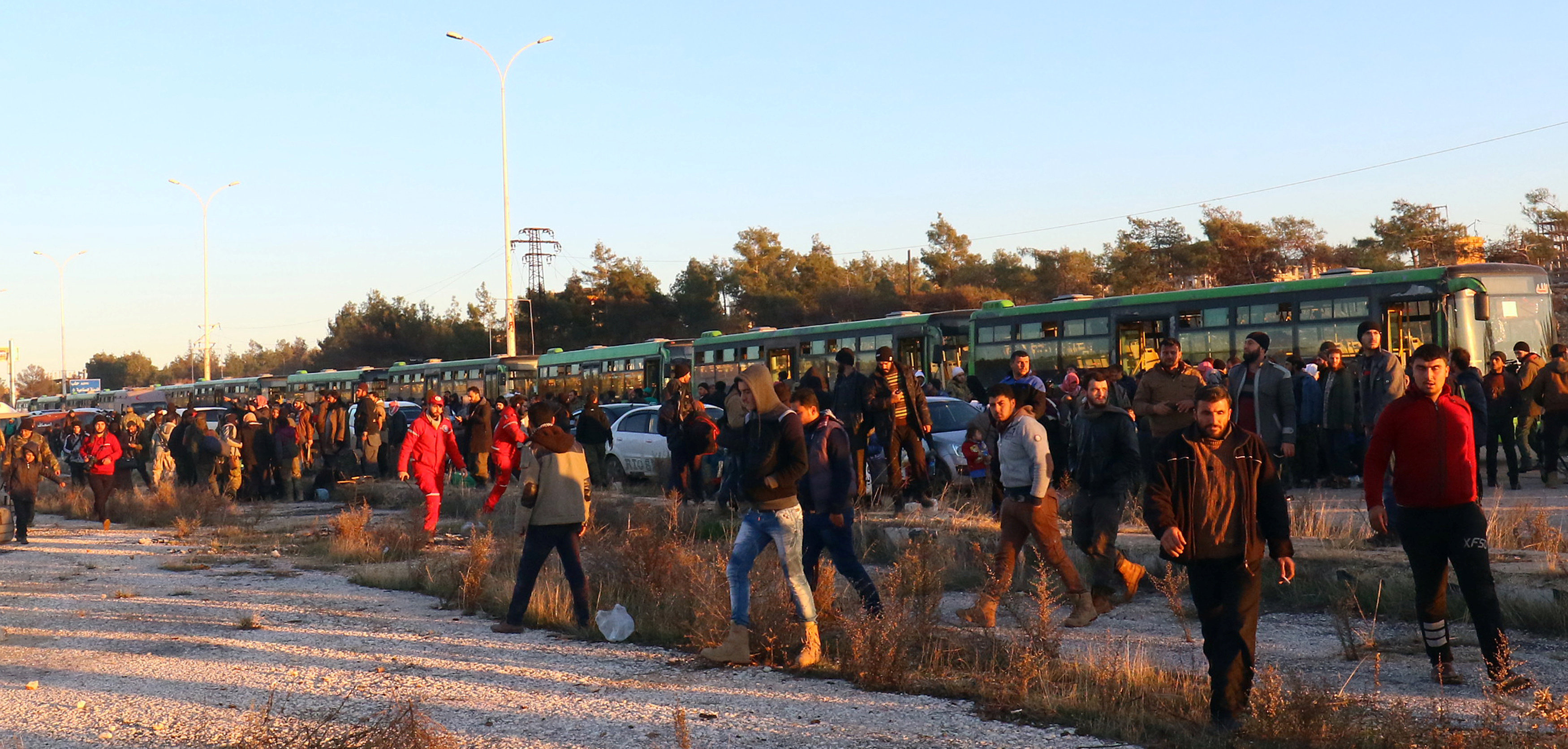 Evacuees from rebel-held east Aleppo, disembark from buses upon their arrival to the town of al-Rashideen, which is held by insurgents, Syria December 15, 2016.