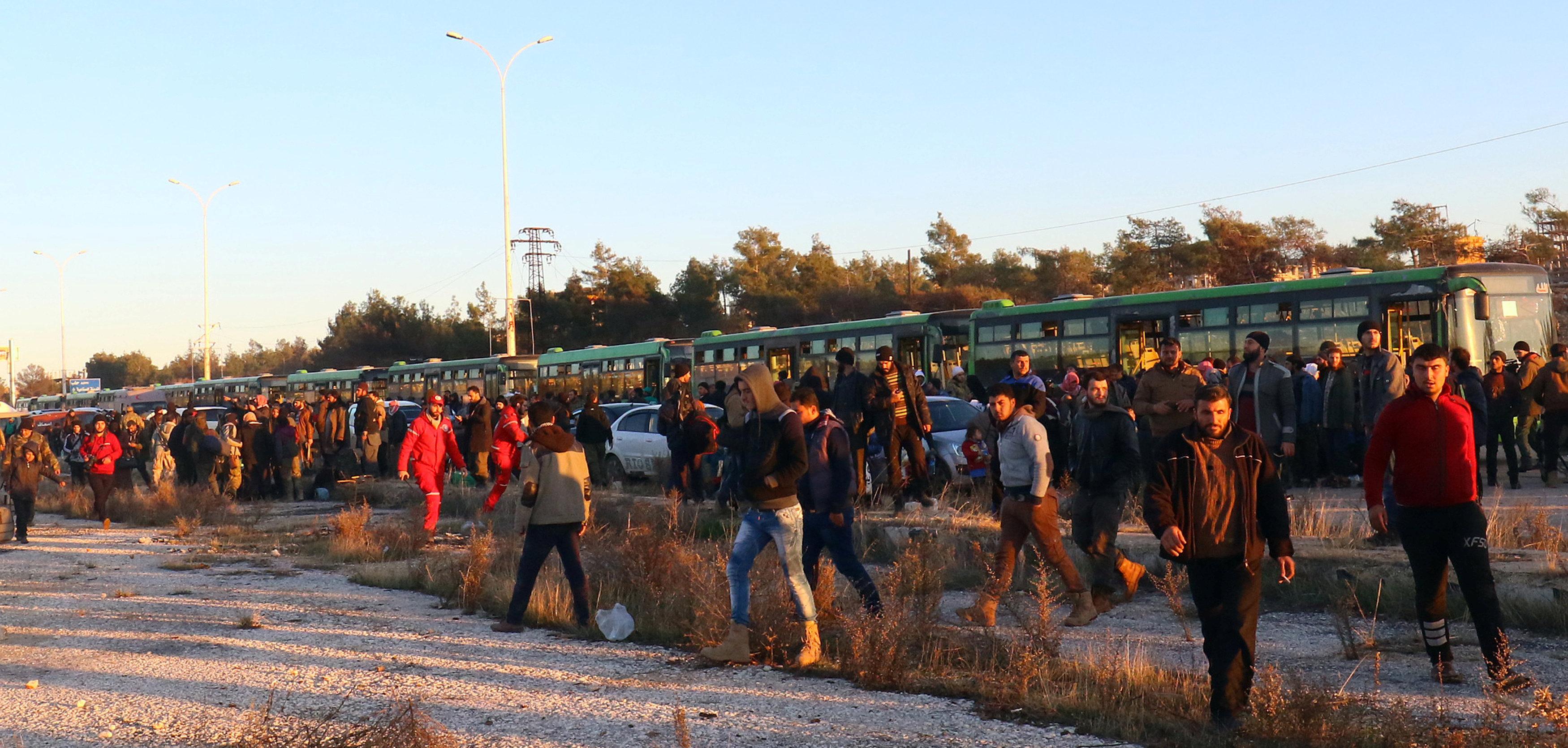 反乱軍の東アレッポからの避難民は、2016年12月15日、シリアの反政府勢力によって保有されているアル・ラシデンの町に到着するとバスから降りる。