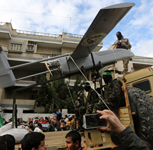 Palestinian militants of the Ezzedine al-Qassam Brigades, Hamas' armed wing, dislpay a drone during a parade marking the 27th anniversary of the Islamist movement's creation on December 14, 2014 in Gaza City