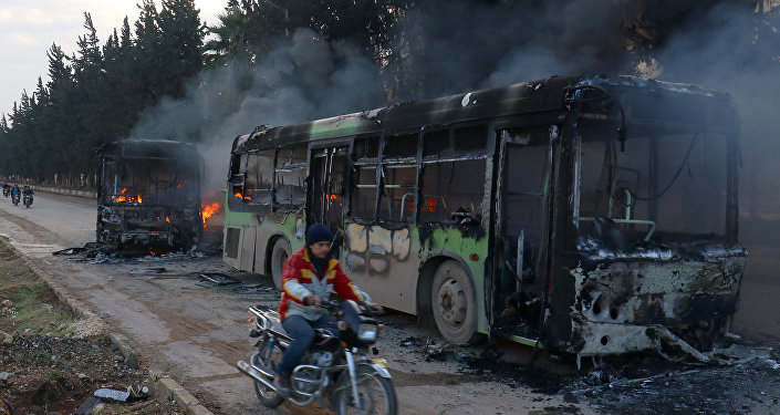 A man on a motorcycle drives past burning buses while en route to evacuate ill and injured people from the besieged Syrian villages of al-Foua and Kefraya, after they were attacked and burned, in Idlib province, Syria December 18, 2016
