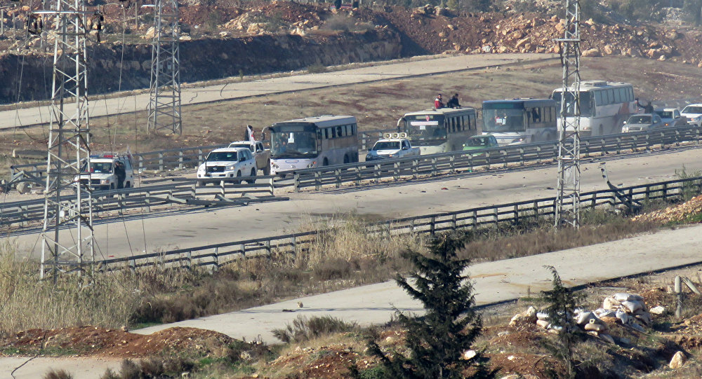 Four buses, with on board people who are evacuated from Fuaa and Kafraya (two under rebel siege Shiite villages), arrive at the Syrian government-controlled crossing of Ramoussa, on the southern outskirts of Aleppo, on December 19, 2016 during an evacuation operation of rebel fighters and civilians from rebel-held areas