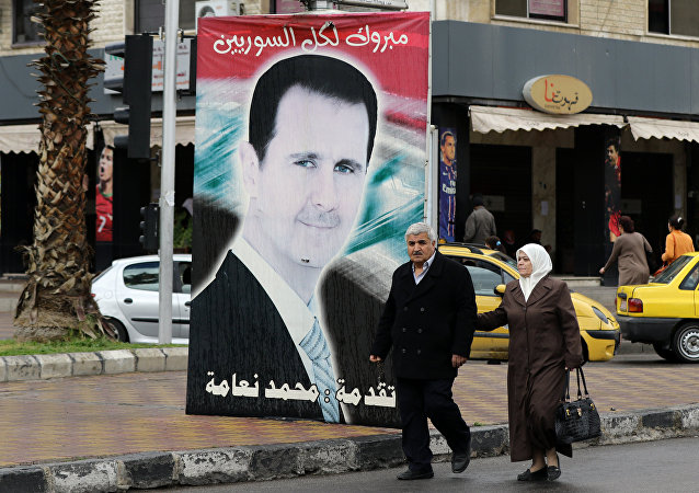 Syrians walk past a portrait of President Bashar al-Assad in the capital Damascus.