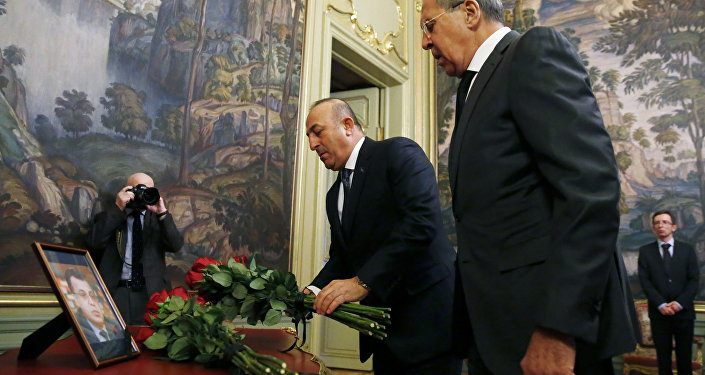 Russian Foreign Minister Sergei Lavrov (R) and his Turkish counterpart Mevlut Cavusoglu lay flowers in front of a photo of Russian ambassador to Turkey, who was killed in Ankara, before their talks in Moscow on December 20, 2016
