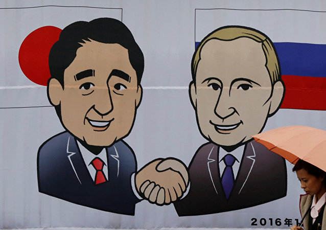 A woman walks past a banner showing Japan's Prime Minister Shinzo Abe and Russian President Vladimir Putin at the Senzaki station in Nagato, Yamaguchi prefecture, Japan, December 14, 2016