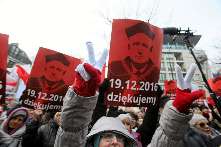 People hold signs with the image of Andrzej Rzeplinski, head of Poland's Constitutional Court, as they take part in demonstration in front of the Constitutional Tribunal in Warsaw, Poland December 18, 2016.