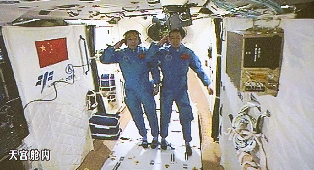 Nesta imagem tirada da tela no Centro de Controle Aeroespacial de Pequim na quarta-feira, 19 de outubro de 2016 e lançado pela Agência de Notícias Xinhua, dois astronautas chineses Jing Haipeng, à esquerda e Chen Dong saudação no laboratório espacial Tiangong 2