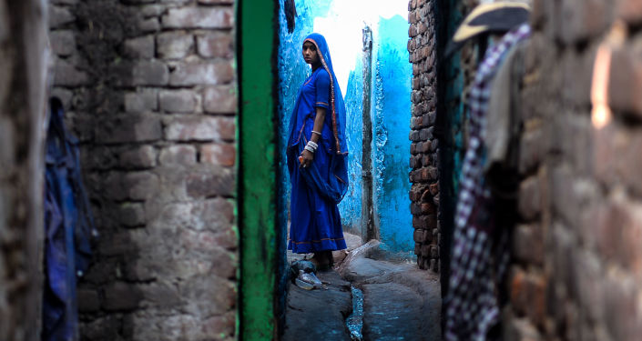 An Indian woman looks on as she stands outside her house in the Kathputli Colony in New Delhi on December 20, 2016