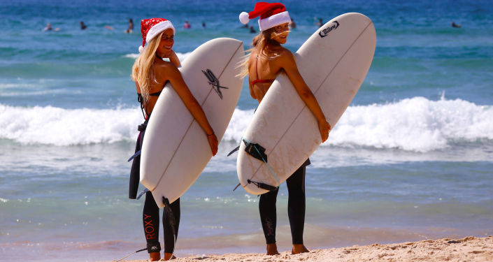 German tourists Mimi Wiebeling (L) and Pauline Lapetite carry surfboards as they walk into the surf wearing Christmas hats at Sydney's Bondi Beach on Christmas Day in Australia