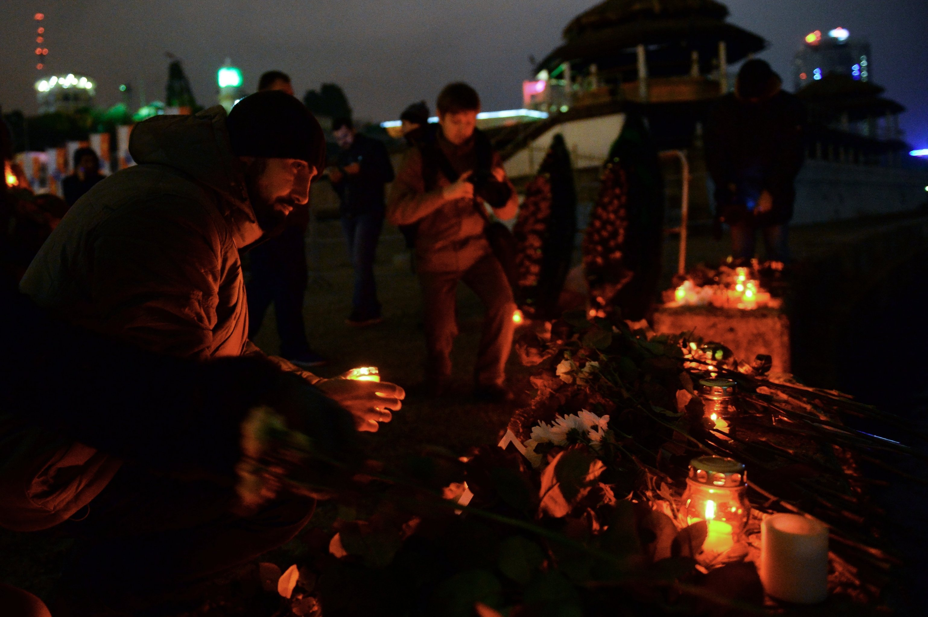 People place candles to honour passengers and crew members of Russian military Tu-154 plane crashed into the Black Sea on its way to Syria on Sunday,  in the resort city of Sochi, Russia