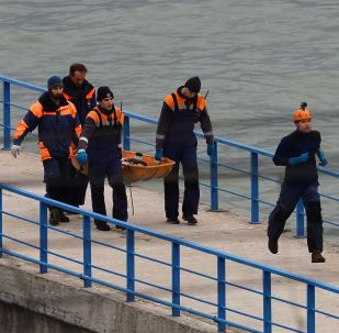 Rescueers carry the body of a victim of Russian Defense Ministry's TU-154 crash on the Black Sea coast off Sochi