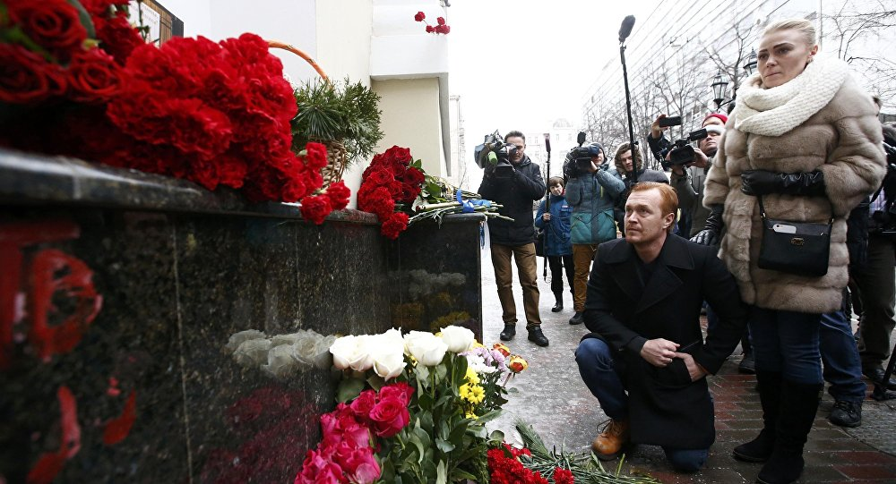 People pay tribute to passengers and crew members of Russian military Tu-154 plane crashed into the Black Sea, near a makeshift memorial outside the headquarters of the Alexandrov Ensemble, also known as the Red Army Choir, in Moscow, Russia December 25, 2016