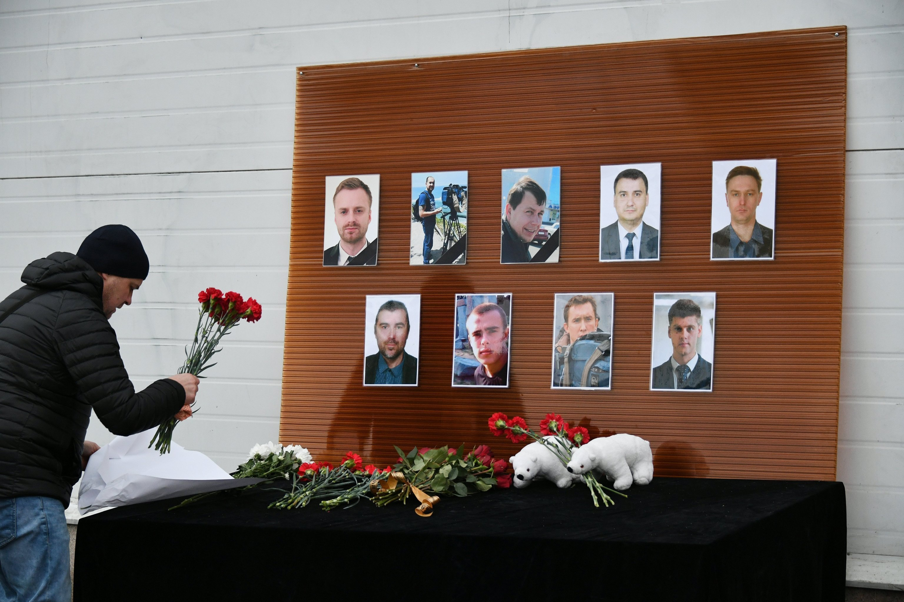 A man outside the Ostankino TV Center lays flowers at the photos of the journalists who died in the Russian Defense Ministry's TU-154 aircraft crash off the Black Sea coast near Sochi