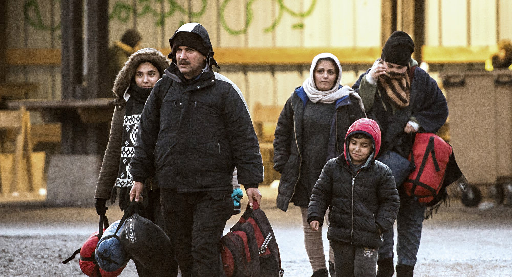 Migrants walk in a refugee camp on December 14, 2016 in Grande-Synthe, northern France