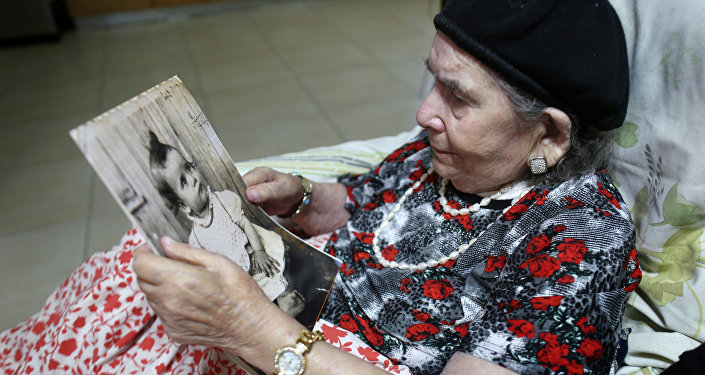 Frecha Amar, 84, from a Moroccan descent, poses with a picture of her baby, who she says was abducted in 1958, on June 29, 2016 at her home in Kfar Chabad, near Tel-Aviv