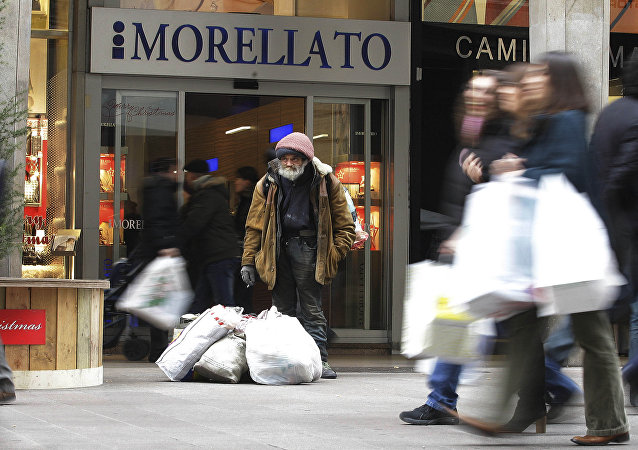 A beggar stands in Vittorio Emanuele shopping street in Milan, Italy, Wednesday, Dec.21, 2011