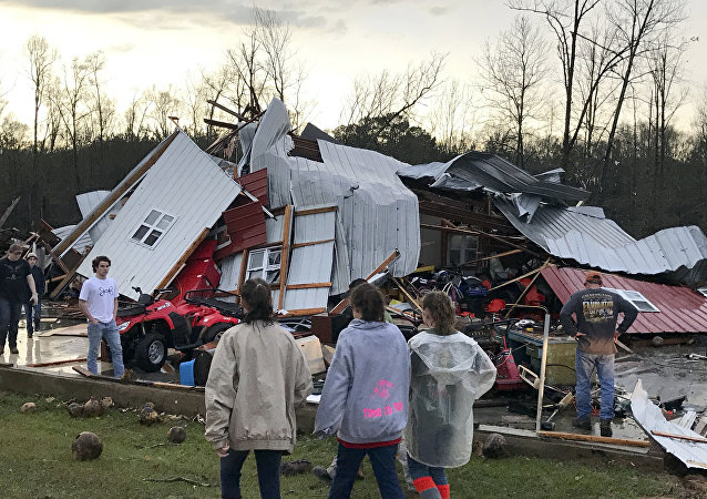 People examine a barn owned by the Miller family that was destroyed during a storm south of Mount Olive, Miss., Monday, Jan. 2, 2017