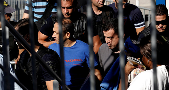 Two of the eight Turkish soldiers, who fled to Greece in a helicopter and requested political asylum after a failed military coup against the government, are escorted by special police forces after the postponement of their interviews for asylum request at the Asylum Service in Athens, Greece, July 27, 2016