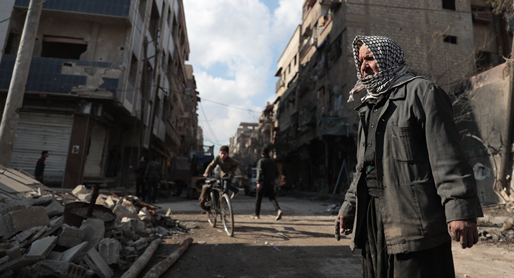 Syrian Abu Khaled looks at the rubble of his destroyed house in the rebel-held town of Douma, on the eastern outskirts of Damascus, on December 30, 2016, on the first day of a nationwide truce