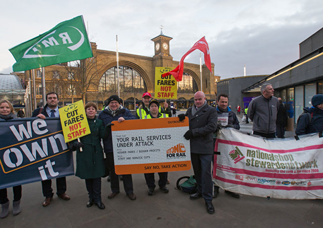 Protestors hold placards as they demostrate against the annual rise in rail tickets, for travel on trains, outside King's Cross railway station in London on January 3, 2017