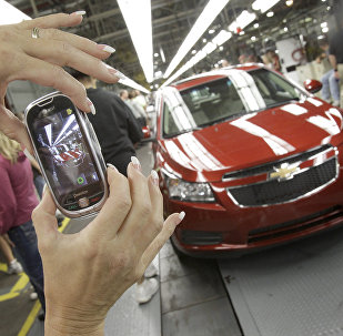 In this Sept. 8, 2010 file photo, auto worker Brenda Hedland takes a picture of the first Chevrolet Cruze compact sedan to come off the assembly line at a ceremony inside the GM factory in Lordstown, Ohio
