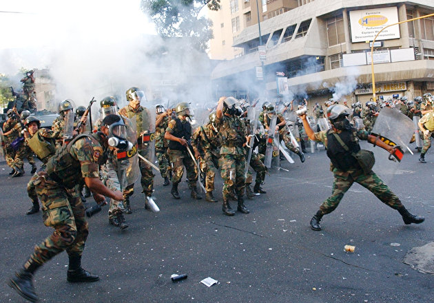 National Guards throw tear gas at President Hugo Chavez supporters during a protest near the Supreme Court in Caracas, Venezuela, Wednesday, Aug. 14, 2002. The supporters were protesting against the Supreme Court's decision to dismiss all charges against four military officers accused of leading an April coup against Chavez.