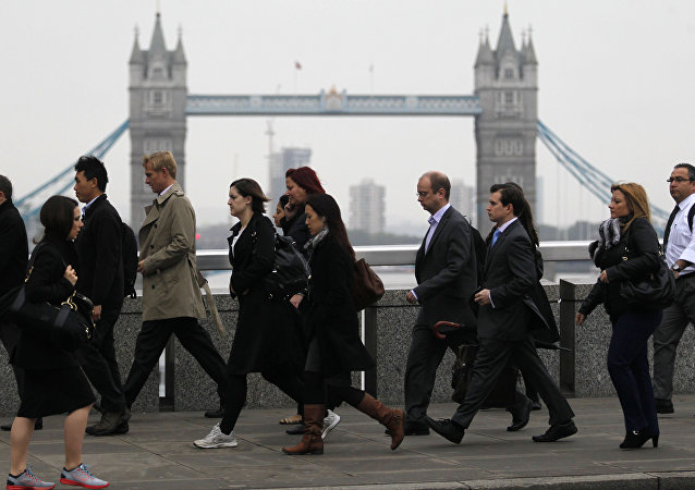 Workers walk across London Bridge on their way to the City of London, Thursday, Oct. 25, 2012