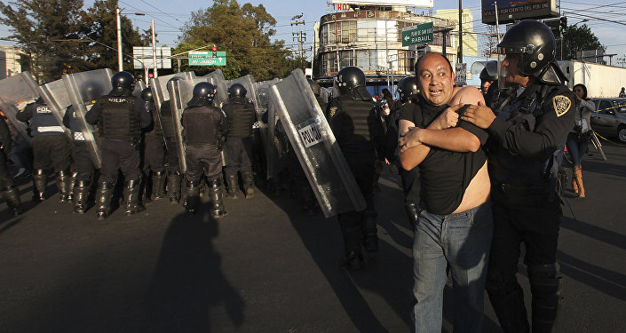 Police remove demonstrators who blocked a main road for about an hour during protests against gas price hikes in Mexico City, Wednesday, Jan. 4, 2017