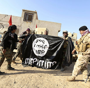 Iraqi Army soldiers celebrate as they hold a flag of the Islamic State group they captured during a military operation to regain control of a village outside Mosul, Iraq (File)