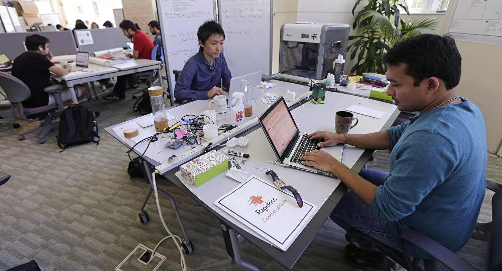 In this Thursday, June 30, 2016 photo, Babson College graduate school alumnus Abhinav Sureka, of Mumbai, India, right, types in his work space at the college in Wellesley, Mass. Some U.S. colleges are starting programs to help their alumni get visas through what critics say is a legal loophole
