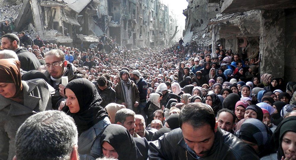 Palestine Refugees in the Near East (UNRWA), residents of the besieged Yarmouk refugee camp near Damascus, Syria, queue to receive food supplies (File)