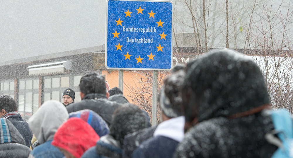 Migrants heading to Germany during a snow shower at the German-Austrian border near Wegscheid, Germany, Saturday Nov. 21, 2015