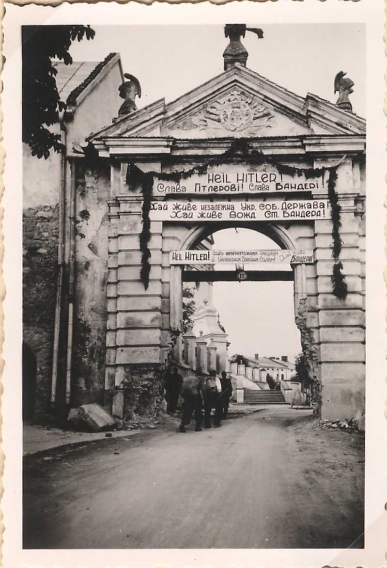 Geetings over a city archway in western Ukraine reading Hail to Hitler! Glory to Bandera!. July-August 1941