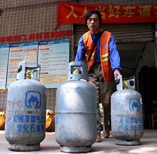 A worker delivers cylinders of liquefied petroleum gas (LPG) at a LPG service station in Guangzhou, southern China's Guangdong province. (File)