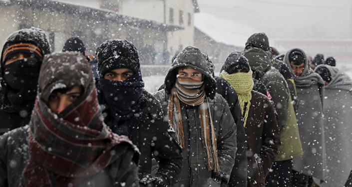 Migrants wait in line to receive free food during a snowfall outside a derelict customs warehouse in Belgrade, Serbia January 9, 2017