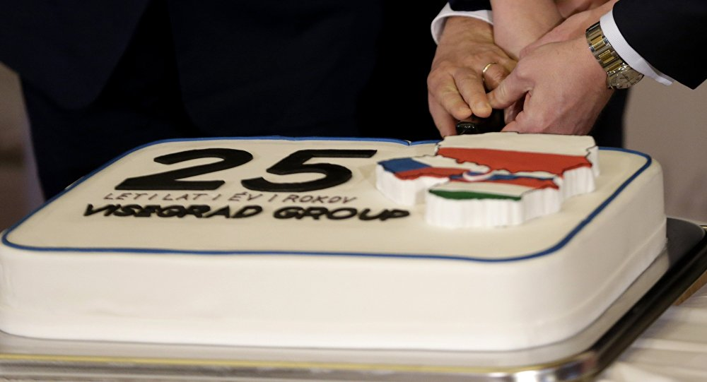 Prime Ministers of Czech Republic Bohuslav Sobotka, Poland Beata Szydlo, Hungary Viktor Orban, and Slovakia Robert Fico, join hands to cut a cake to celebrate 25th anniversary of the establishment of the Visegrad group prior to a Summit of the V4 Prime Ministers with the Prime Minister of Bulgaria and the President of Macedonia in Prague, Czech Republic, Monday, Feb. 15, 2016
